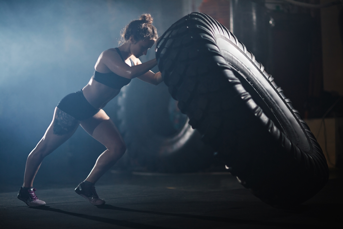 "An athletic woman with a thigh tattoo is flipping a tire and plagued by her ""no pain, no gain"" attitude"