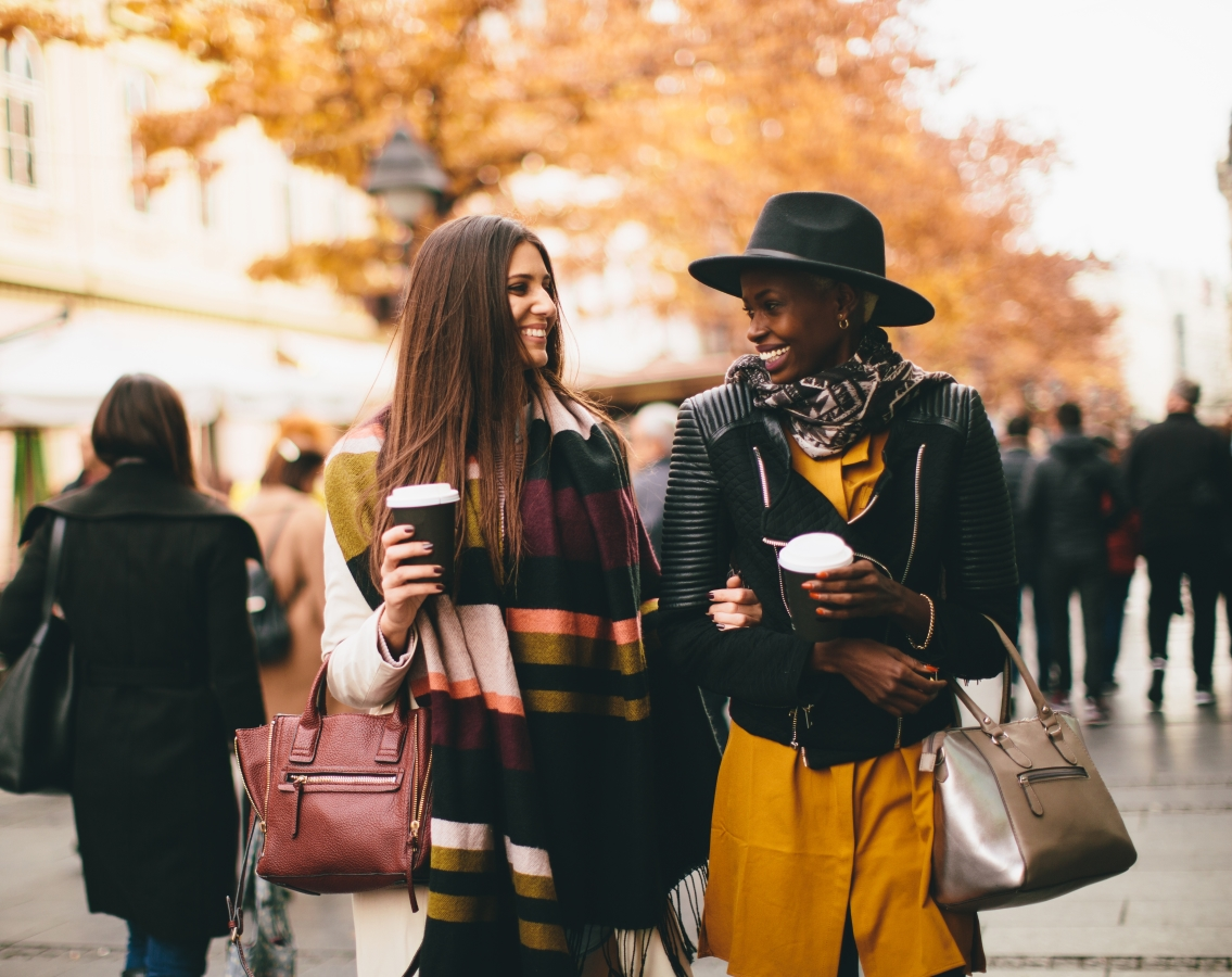Two women walking with to-go cups of coffee in fall weather discussing tips to survive the upcoming holidays