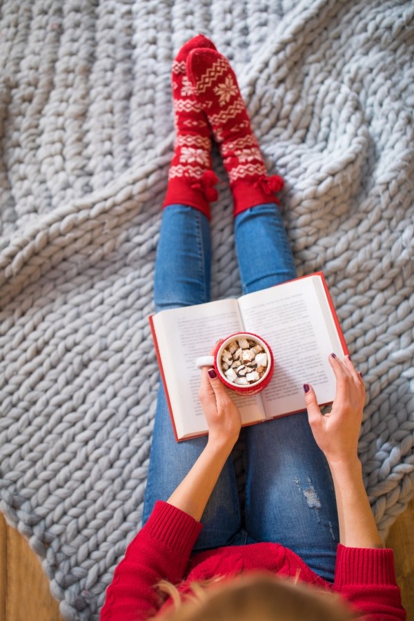 Woman sitting on a blanket in cozy holiday sucks with a cup of hot chocolate thinking about holiday survival tips