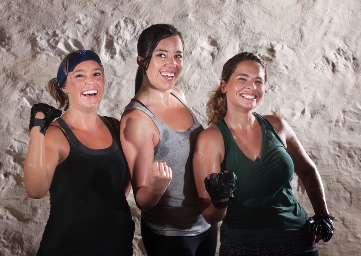 Three women of different sizes and heights are flexing and smiling while wearing sweaty workout gear