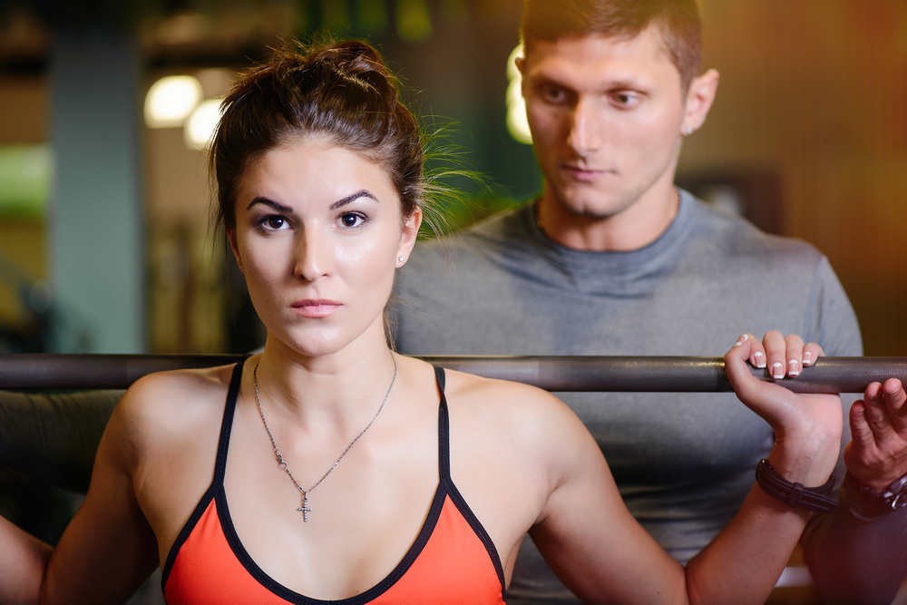 Woman with a barbell on her back being creepily watched by a muscular guy standing just over her shoulders