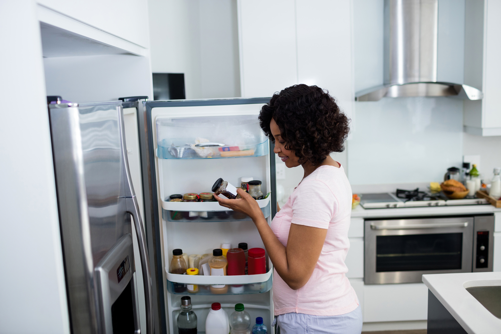 A woman standing next to her open refrigerator door looking at a jar