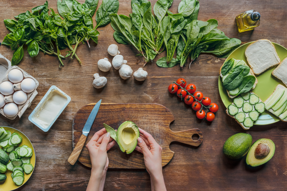 A woman's hands cutting an avocado with a spread of fresh vegetables and eggs because she has not commited to stop dieting
