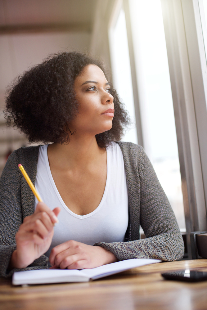 A woman staring out the window while journaling about what she had learned from overeating and holding a pencil