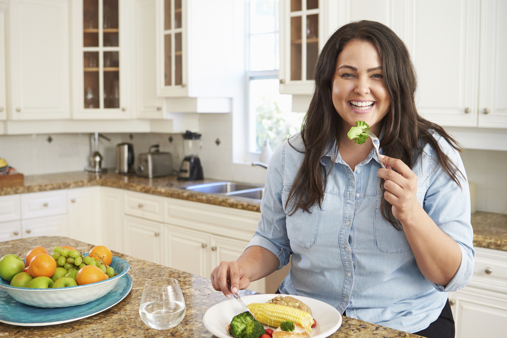 A smiling woman happily eats from a plate of veggies in her kitchen because she is not afflicted with an obsession with superfoods