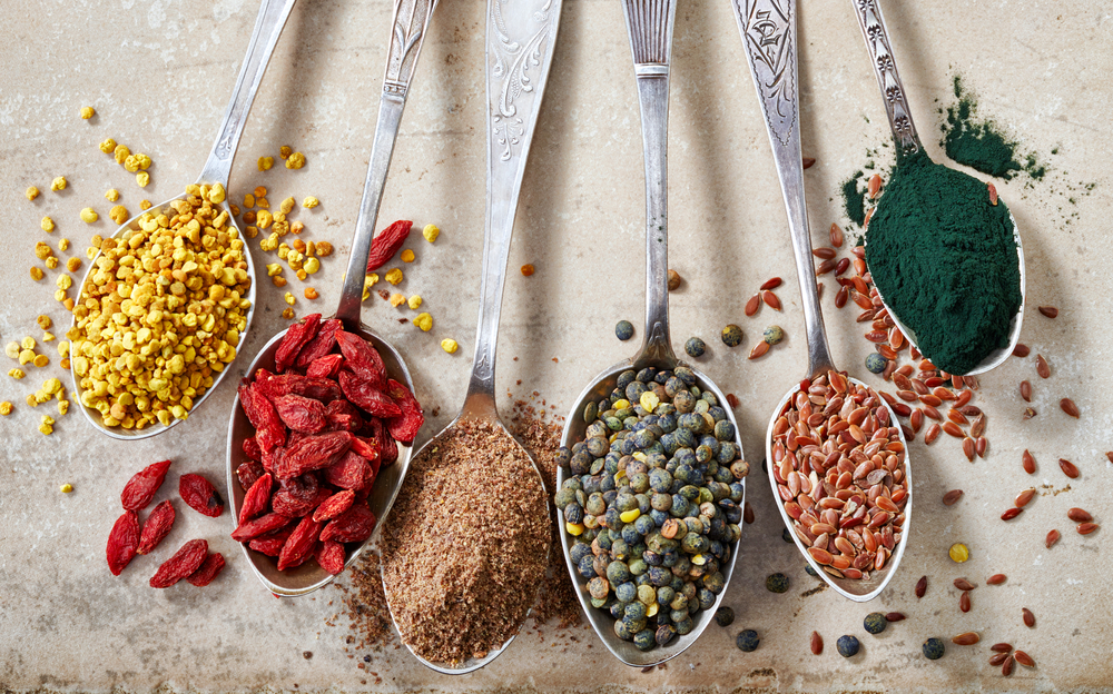 Various colorful superfoods arranged on silver spoons that people tend to have an unhealthy obsession with