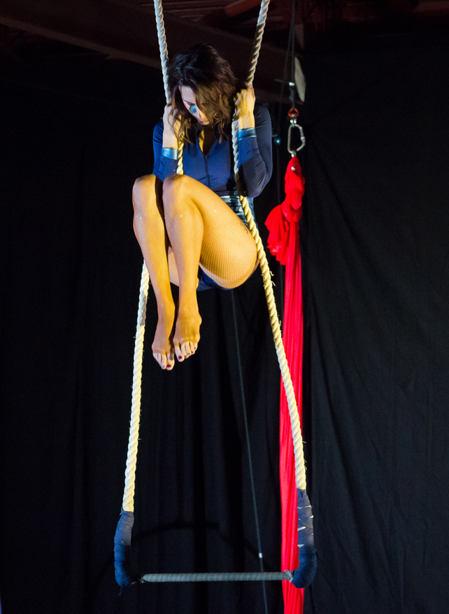Shohreh holds herself in the trapeze ropes in a tight ball