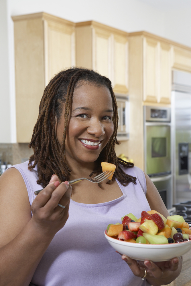 A woman in a purple shirt eats a fruit salad in her kitchen feeling grateful for her weight-inclusive coach