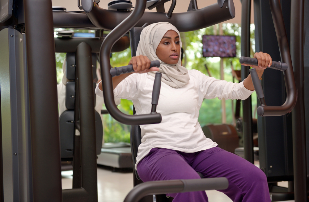 A woman wearing a hijab using a chest press machine at a gym because strength is one of her reasons to exercise