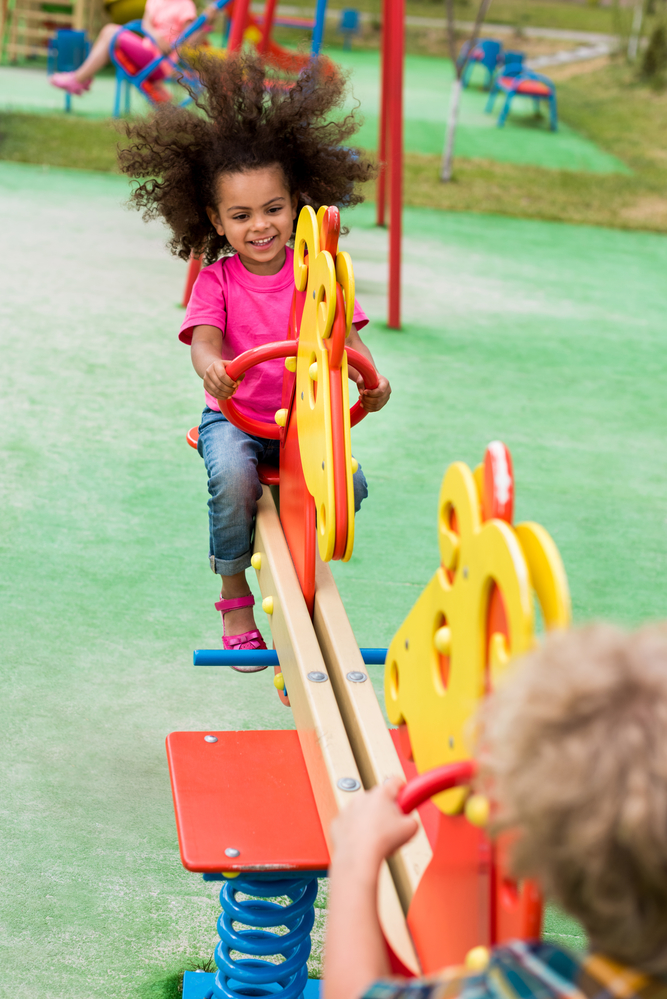 A little girl playing on a seesaw with hair flying behind her
