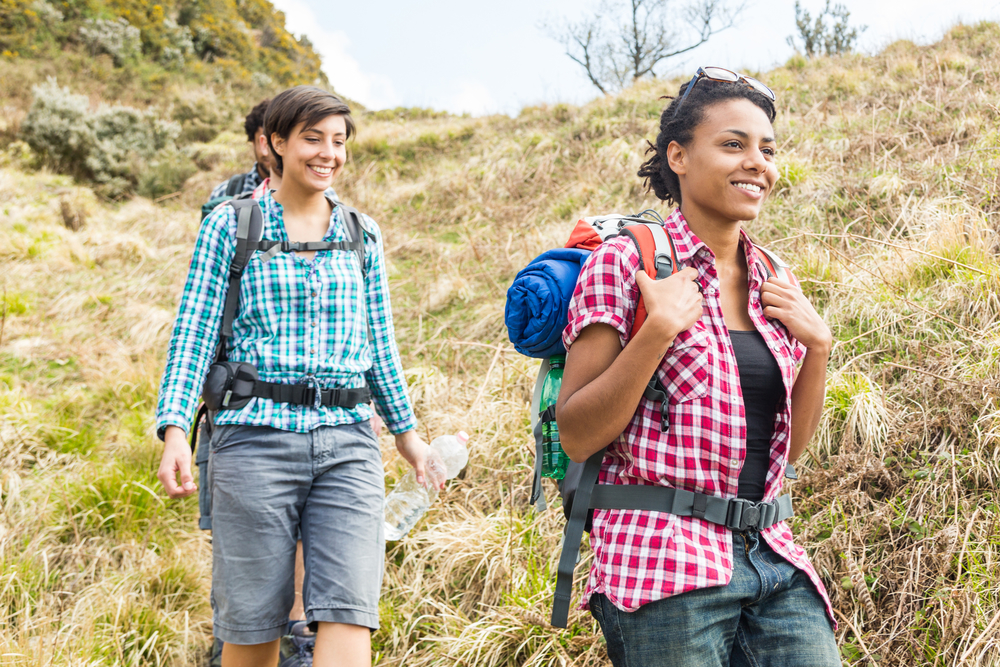 A group of three friends smiling and hiking down the side of a hill
