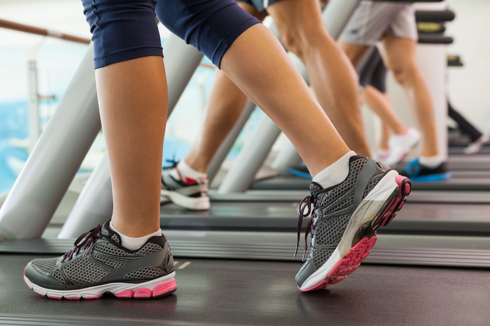 Row of legs of people walking on treadmills at the gym, pondering their reasons to exercise