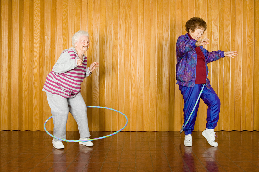Two senior women wearing sweats and exercising with hula hoops because fun is one of their reasons to exercise