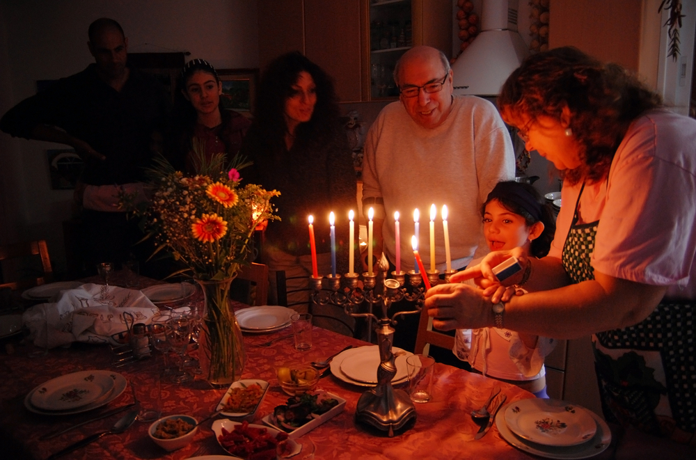 A family gathers around a lit menorah for Hanukkah