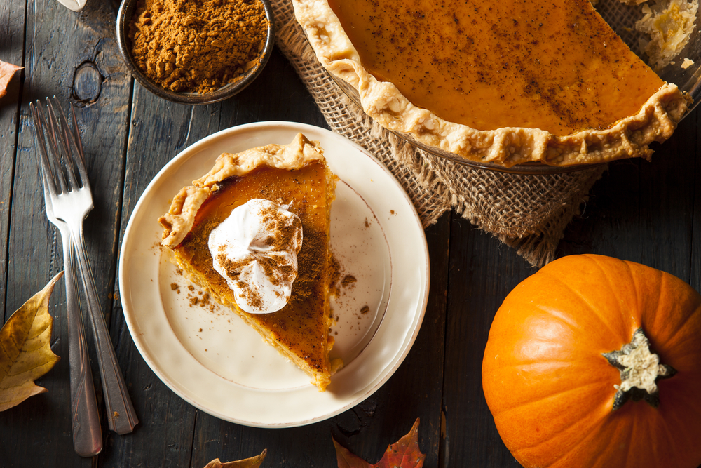 A slice of pumpkin pie with whipped cream on a table with a pumpkin, cinnamon, and forks