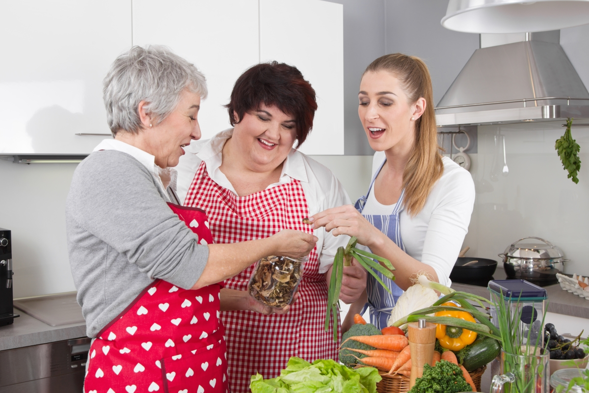 Three women of different generations wearing aprons in the kitchen admire ingredients