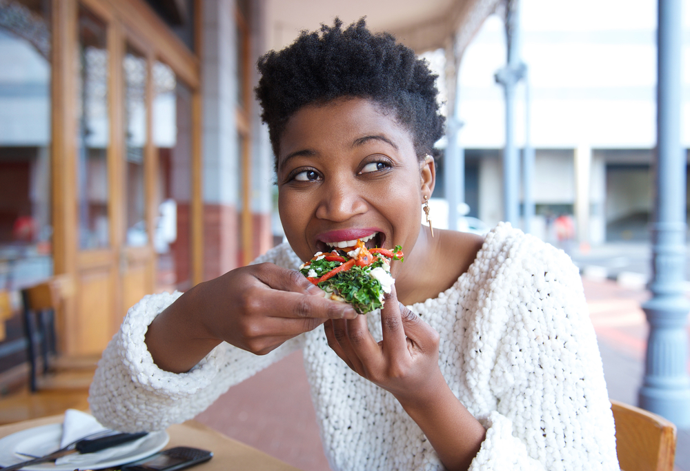 A woman eating pizza at restaurant and not falling for intuitive eating myths